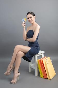 Mooie aziatische vrouw met boodschappentas en creditcard in de hand
