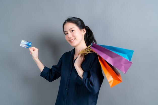 Mooie aziatische vrouw met boodschappentassen en creditcard geïsoleerd tonen