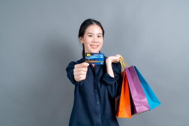 Mooie aziatische vrouw met boodschappentassen en creditcard tonen die op grijze muur wordt geïsoleerd