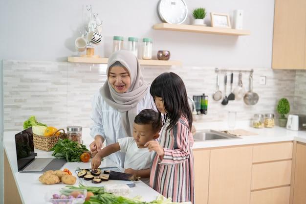 Mooie aziatische vrouw met dochter en zoon die diner koken tijdens ramadan voor iftar die het vasten breekt
