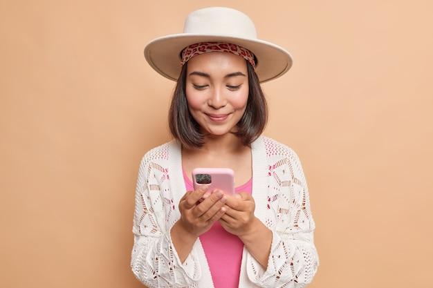 Mooie aziatische vrouw met donker haar houdt moderne mobiele telefoon controleert bericht verbonden met draadloos internet draagt fedora gebreide witte jas geïsoleerd over beige muur maakt gebruik van mobiele applicatie