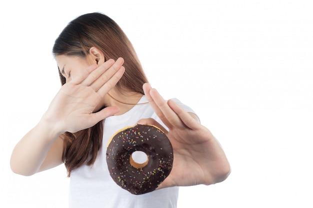 Mooie aziatische vrouw met een gelukkige glimlach, die doughnut in hand houdt