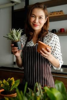 Mooie aziatische vrouw met een schort die kleine planten en bloemen in de tuin vasthoudt en toont met een glimlach en een blij gezicht. hobby en vrije tijd werkconcept.