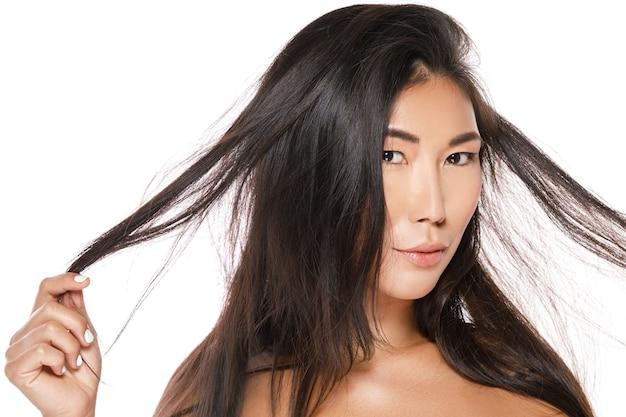 Mooie aziatische vrouw met gezond zwart haar op witte muur