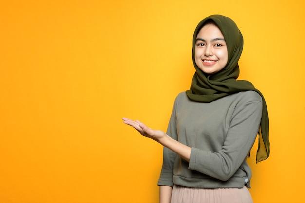 Mooie aziatische vrouw met glimlachend en product tonen