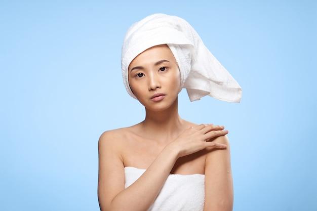 Mooie aziatische vrouw met handdoek op hoofd op blauwe achtergrond.