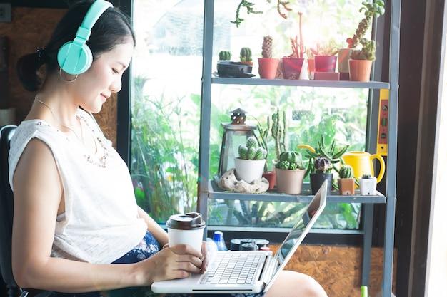 Mooie aziatische vrouw met hoofdtelefoons die op film letten door laptop computer.