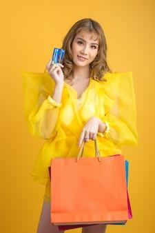 Mooie aziatische vrouw met in hand het winkelen zak en creditcard
