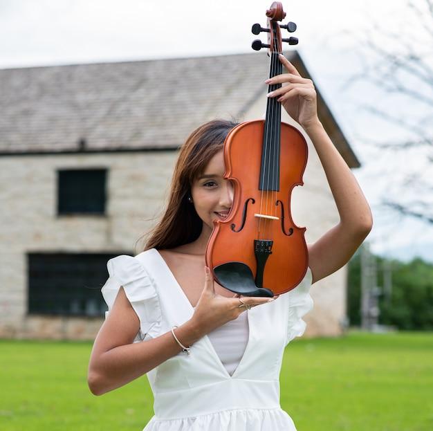 Mooie aziatische vrouw met lang haar speelt een viool