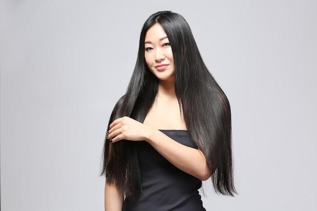 Mooie aziatische vrouw met lang steil haar op lichte achtergrond