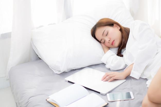 Mooie aziatische vrouw met laptop die in slaapkamer ligt