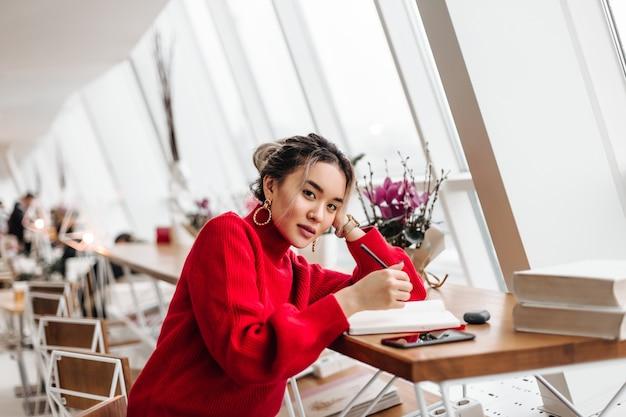 Mooie aziatische vrouw met paardenstaart gekleed in rode oversized trui zit in co-werkruimte en maakt aantekeningen in notitieblok