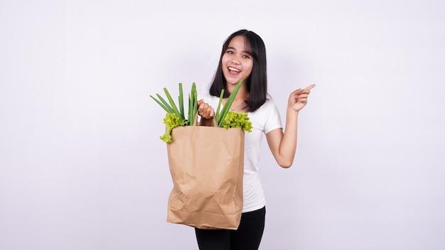 Mooie aziatische vrouw met papieren zak met verse groenten erg blij wijzend met de hand en vinger op geïsoleerde witte ondergrond