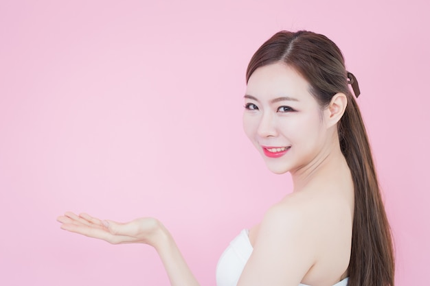 Mooie aziatische vrouw met perfecte huid. glimlachmeisje dat lege exemplaarruimte toont die uw product voorstelt