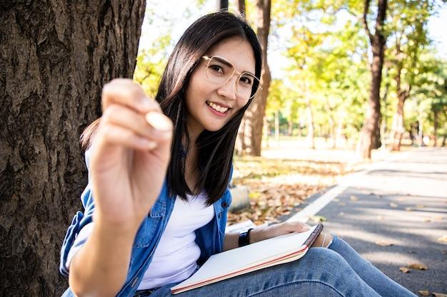 Mooie aziatische vrouw met potlood en dagboek schrijven op laptop met heldere glimlach gezicht in openbaar park ze leren en hard werken in het laatste weekend lente seizoen warme toon