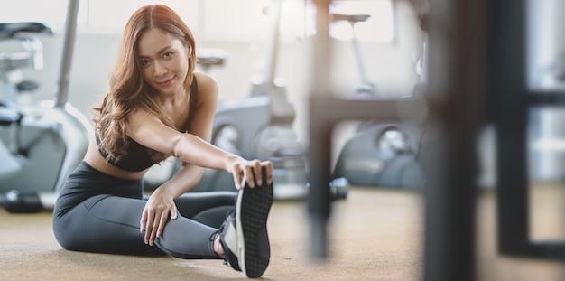 Mooie aziatische vrouw met tan en slanke lichaam uitrekkende benen vóór oefening