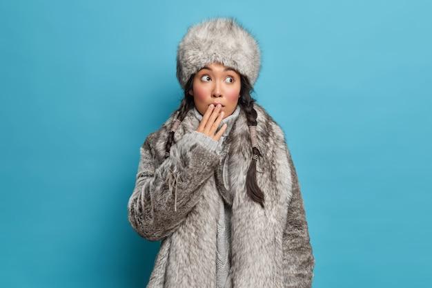 Mooie aziatische vrouw met twee staartjes bedekt mond en voelt geschokt draagt warme natuurlijke bontjas en hoed jurken voor koud weer woont in het noorden geïsoleerd over blauwe muur