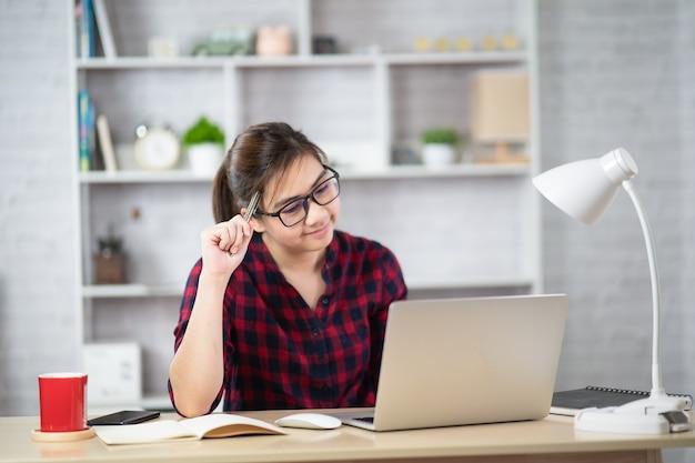 Mooie aziatische vrouw ontspannen met behulp van laptopcomputer zittend op tafel. creatief meisje dat werkt en typt op toetsenbord thuis. werk thuis concept