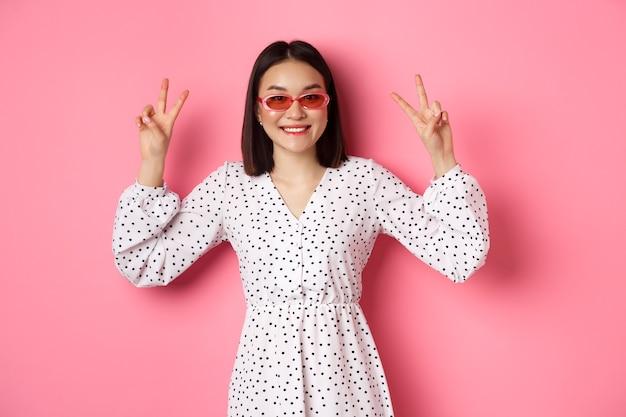 Mooie aziatische vrouw op zomervakantie, vredestekens tonen en gelukkig glimlachen, trendy zonnebril dragen, roze.