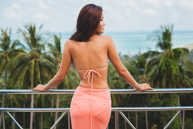 Mooie aziatische vrouw poseren in roze bikini zwembroek en pareo op terras op tropische villa glimlachend gelukkig op vakantie in thailnad, sexy lichaam zomer stijl, uitzicht vanaf achterkant, kijkend op landschap