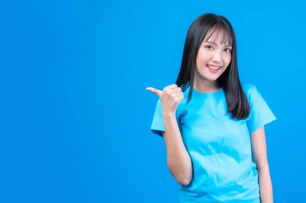 Mooie aziatische vrouw schattig meisje met pony kapsel in blauw t-shirt glimlachend en wijzende vinger naar lege kopie ruimte voor huidig product of lege ruimte voor reclame geïsoleerd op blauwe achtergrond