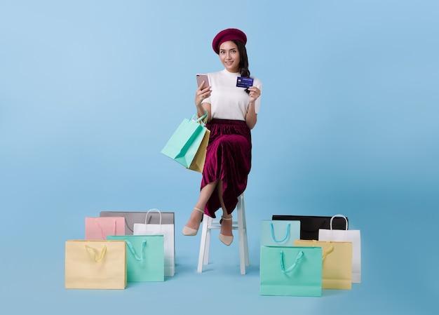 Mooie aziatische vrouw shopper zitten en boodschappentassen dragen met creditcard en mobiele telefoon in handen op blauwe achtergrond.