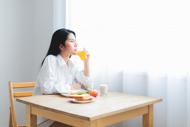 Mooie aziatische vrouw. thaise dame die witte pyjama draagt. drink sinaasappelsap in de eetkamer. ontbijt op tafel