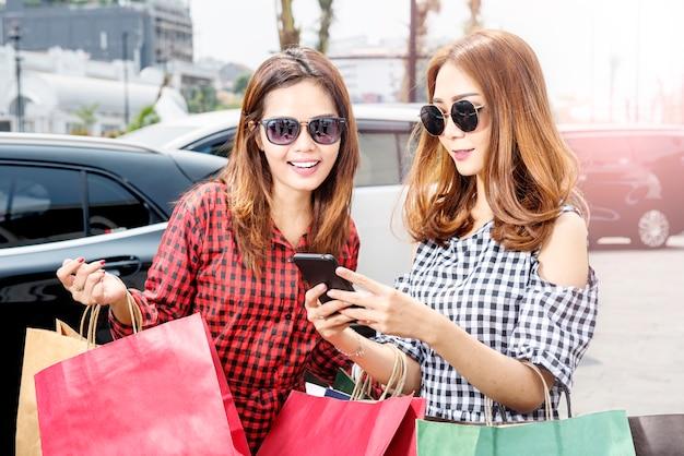 Mooie aziatische vrouw twee in zonnebril die de telefoon bekijken terwijl het dragen van het winkelen zakken
