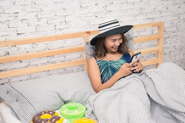 Mooie aziatische vrouw wat betreft tablet slimme telefoon en het eten van popcorn op bed