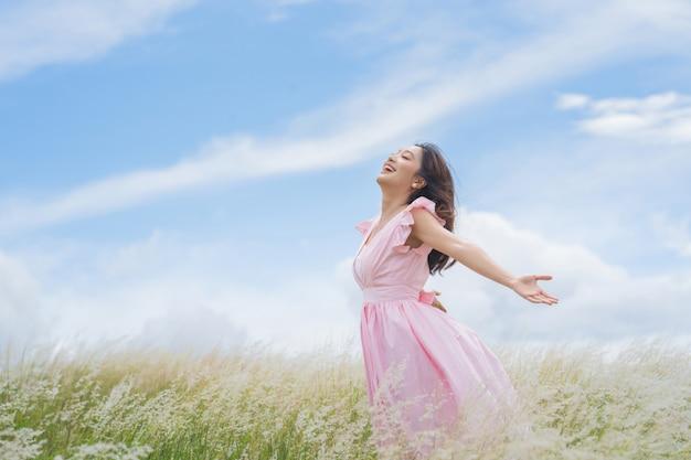 Mooie aziatische vrouw ze heeft vrijheid op de weide. ze is gelukkig.