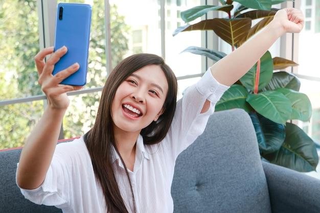 Mooie aziatische vrouw zit en ontspan op de bank in de woonkamer van het huis. ze houdt een smartphone vast om foto's van zichzelf te maken. geniet van het alleen zijn. concept van het gebruik van moderne communicatiemiddelen