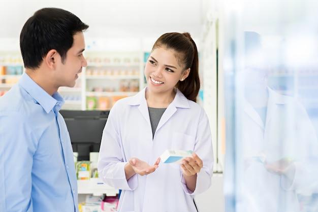 Mooie aziatische vrouwelijke apotheker met klant in een apotheek.