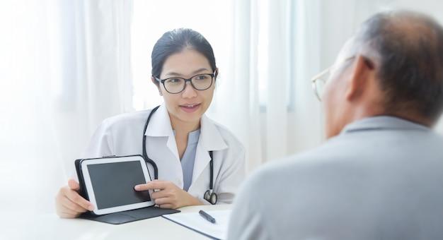 Mooie aziatische vrouwelijke arts die wat informatie over virus geeft aan bejaarde patiënt met digitale tablet.