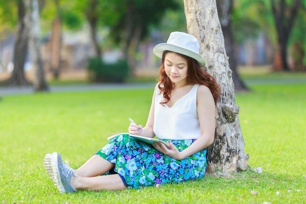 Mooie aziatische vrouwelijke handen met een pen schrijvend notitieboekje en zij zat buiten op gras