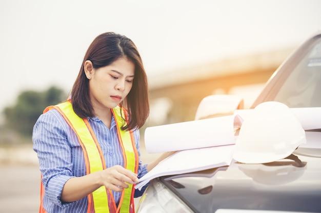 Mooie aziatische vrouwelijke ingenieur in witte veiligheidshelm doet werk op bouwplaats buiten kantoor. idee voor moderne werkende vrouw hightway weg