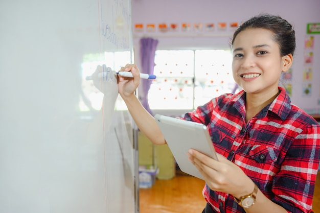 Mooie aziatische vrouwelijke leraarshand die tablet houdt die op whiteboard schrijft die studenten op school in klaslokaal onderwijst voor onderwijs