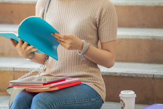 Mooie aziatische vrouwelijke student die haar boeken en een kop van koffie houdt