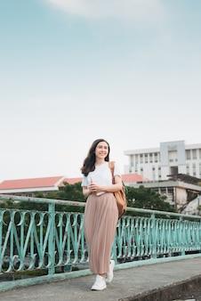 Mooie aziatische vrouwelijke student die haar boeken vasthoudt, staat en kleedt zich in street fashion-doek in de openbare ruimte buiten met een moderne bouwachtergrond