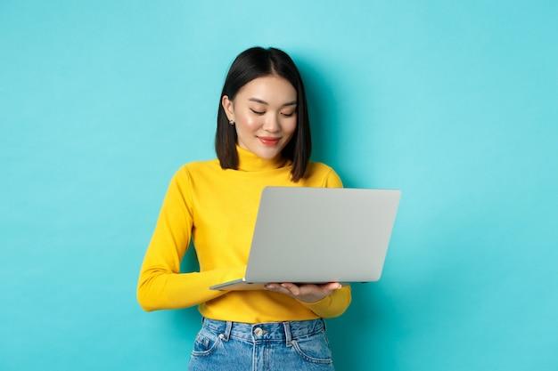 Mooie aziatische vrouwelijke student die op laptop werkt, op toetsenbord typt en naar het scherm kijkt met een tevreden glimlach, staande over blauwe achtergrond