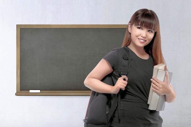 Mooie aziatische vrouwelijke student met rugzak en boek
