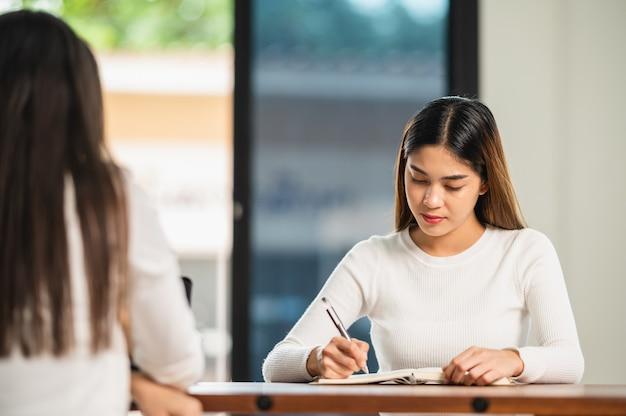 Mooie aziatische vrouwelijke student zit voor examen aan universiteitsklasstudenten die in de rij onderwijslevensstijl hogeschool zitten