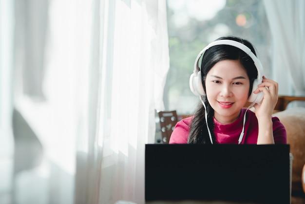 Mooie aziatische vrouwelijke studenten die een koptelefoon dragen terwijl ze online studeren docenten en studenten gebruiken online videoconferentiesystemen om studenten les te geven.