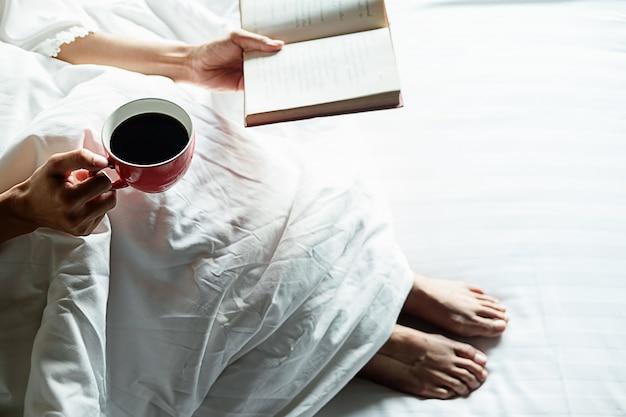 Mooie aziatische vrouwelijke zitten in het bed met een kopje koffie.