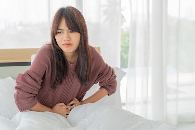 Mooie aziatische vrouwen buikpijn en slapen op bed