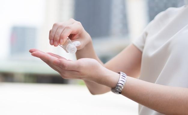 Mooie aziatische vrouwen die een medisch gezichtsmasker dragen, gebruiken alcoholgel of ontsmettingsmiddel om de hand schoon te maken in een openbare ruimte of in het stadscentrum, als nieuwe normale trend