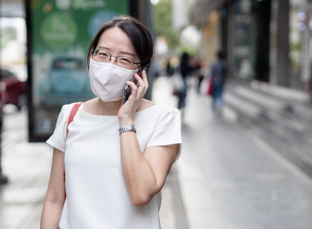 Mooie aziatische vrouwen die een wegwerp medisch gezichtsmasker dragen, met een smartphone terwijl ze zich in een openbare ruimte, langs de weg of in het stadscentrum bevinden, als nieuwe normale trend en zelfbescherming tegen infectie met covid19.