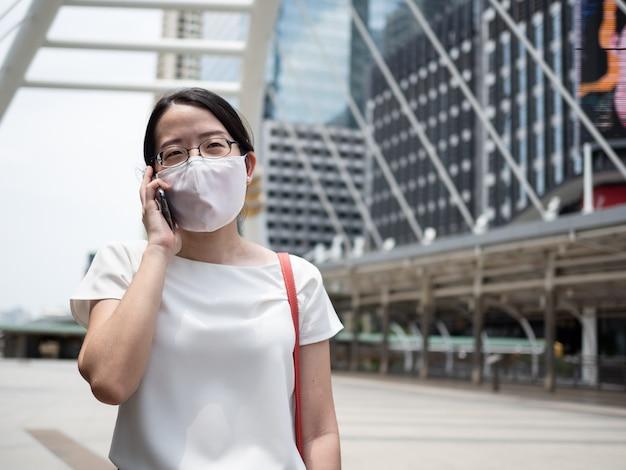 Mooie aziatische vrouwen die een wegwerp medisch gezichtsmasker dragen, terwijl ze een smartphone gebruiken in een openbare ruimte, langs de weg of het stadscentrum, als nieuwe normale trend
