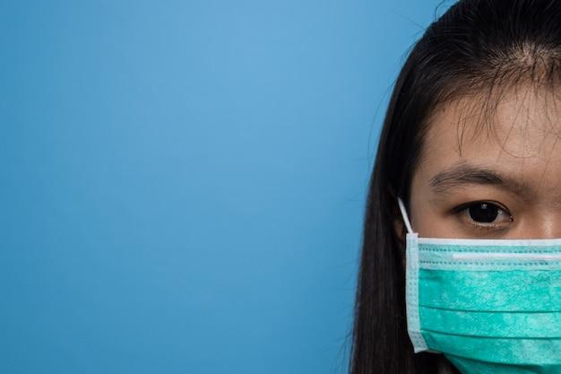 Mooie aziatische vrouwen die een wit t-shirt gebruiken met een blauwe geïsoleerde achtergrond vrouwen die een masker gebruiken covid19