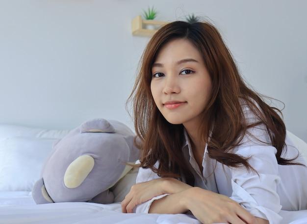 Mooie aziatische vrouwen die in bed op vakantie glimlachen.
