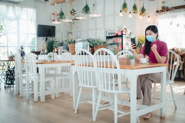 Mooie aziatische vrouwen die maskers dragen online werken in een coffeeshop ze verkoopt vrijelijk online producten, werkt graag thuis tijdens de covid-19-infectie.